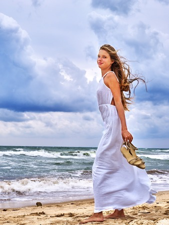 woman sunset: Summer girl sea.  Woman  goes barefoot on coast. Stock Photo