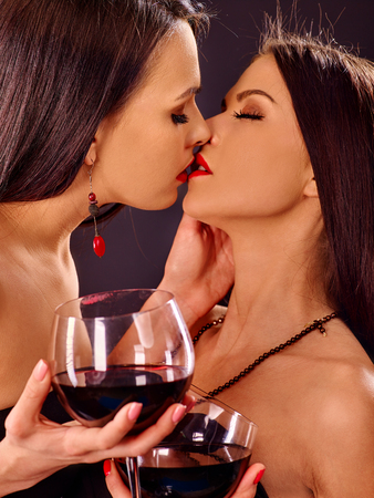 homosexual sex: Two sexy lesbian women drink red wine and kissing. Black background. Stock Photo