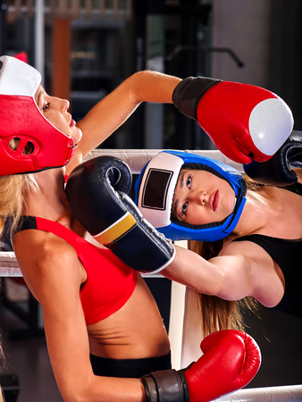 sports venue: Two  women boxer wearing red  gloves to box in ring. Martial arts.