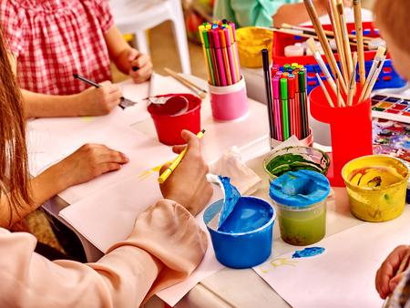 mains Groupe maintient la peinture au pinceau sur la table à la maternelle.