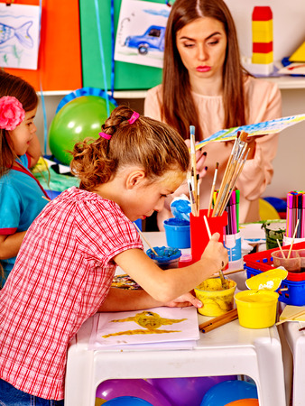 educator: Children with teacher woman painting on paper at table  on craft lesson in  kindergarten . Stock Photo