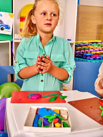 crayon  scissors: Kid molds from plasticine on craft lesson   in kindergarten .