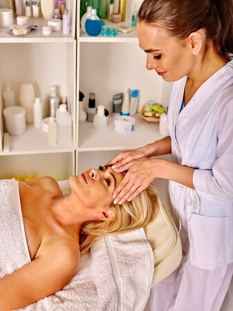 35 40 years old: Woman middle-aged luxuriating on massage of face and neck  in spa salon. Stock Photo