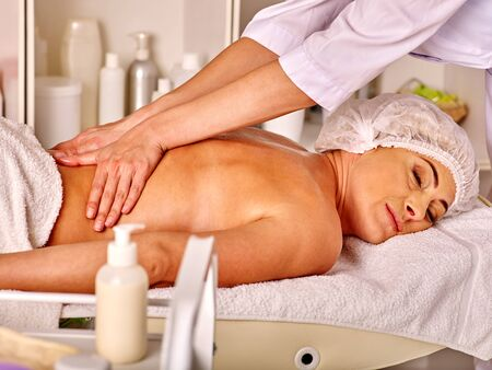 35 40 years old: Woman middle-aged luxuriating on  back massage in spa salon with young beautician.
