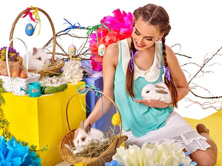 cabeza femenina: Mujer en estilo de Pascua la celebración de los huevos y acariciar conejos en la cesta.