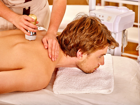 hight tech: Man receiving electroporation back therapy at beauty salon.