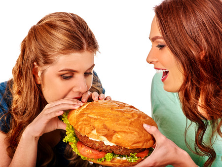 woman eating: Girls bite burger with two sides. Fastfood humor concept.