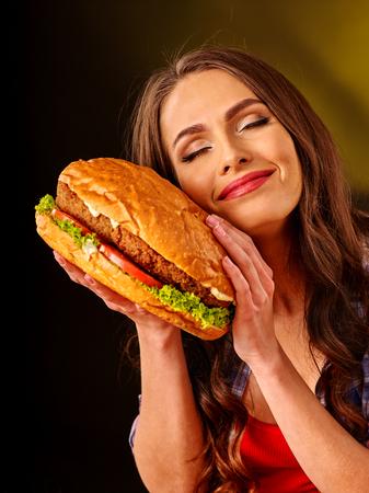 niña comiendo: Chica con los ojos cerrados mantiene hamburguesa grande. concepto de la comida rápida. Foto de archivo