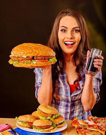 niña comiendo: La muchacha mantiene la comida rápida hamburguesa grande y la bebida. Foto de archivo