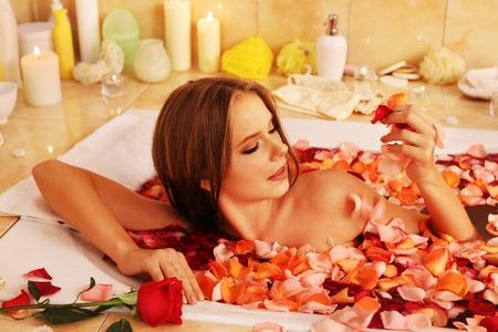 sauna nackt: Junge Frau mit Rosenbl�ttern luxuriating Bad im Spa Salon. Lizenzfreie Bilder