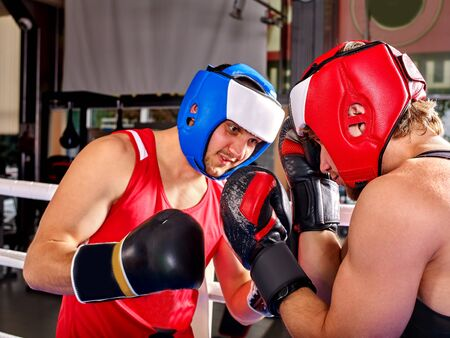 arts and entertainment: Two  men boxer wearing red with blue helmet and  gloves boxing .