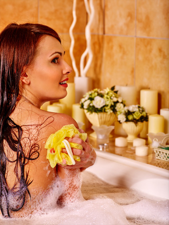 hamam: Young woman keeps sponge take bubble  bath. Woman washing her shoulder. Stock Photo