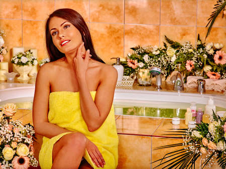 Woman touchs for the neck with your fingers relaxing at water spa. Girl sitting near bath tub. Imagens