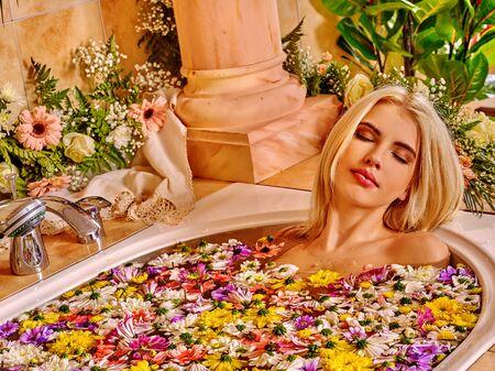 mujer bañandose: Mujer en el agua que se relaja en baño de lujo con flores de spa.