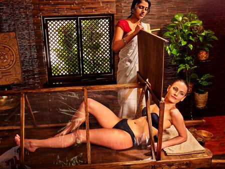 Woman having Ayurvedic sauna treatment. Assistant beautician Hindu.