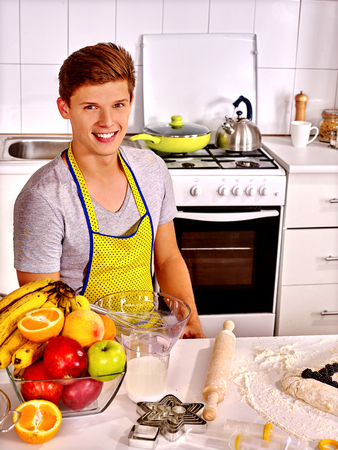 sympathetic: Young sympathetic man  baking cookies in oven. Stock Photo