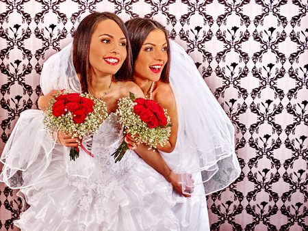 young sex: Wedding lesbians girl in bridal dress keeps bouquet. Wallpaper in background