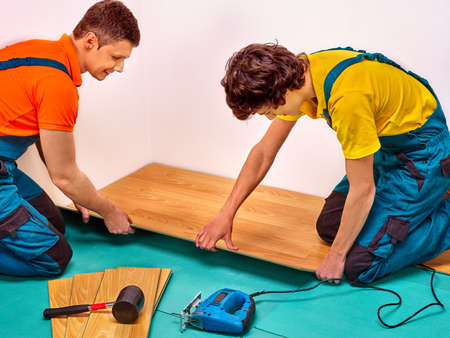 laying: Happy men kneel laying parquet at home.