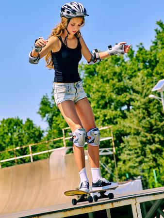 stunt: Teen girl in helmet rides his skateboard outdoor. Girl do  stunt aganist blue sky. Outdoors.