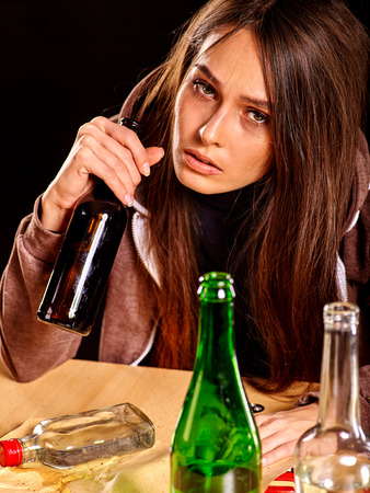 drunk woman: Drunk girl holding bottle of alcohol. Soccial issue alcoholism on black background.