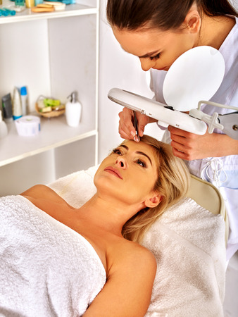 tweezing eyebrow: Lying woman middle-aged in spa salon with young beautician. Tweezing eyebrow by beautician.