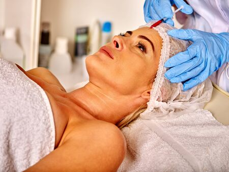 35 40 years old: Lying woman middle-aged in spa salon with beautician. Beauty woman gets anti age injections.