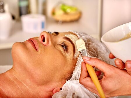 age 35 40 years: Lying woman middle-aged gets facial and neck clay mask in spa salon.