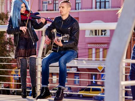 航空ショー: 音楽大道芸人少女バイオリニストと男性ギタリスト屋外都市の背景に。 写真素材
