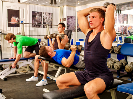 woman mirror: Group of men working his body with dumbbells at gym.