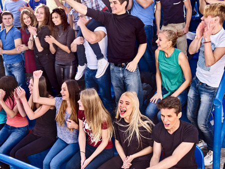 grandstand: Sport young fans boy and girl clapping and singing on tribunes. Group people. Stock Photo
