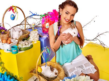 sexy young girl: Женщина с косичками держит пасхальные яйца и группа кроликов в корзине. Фото со стока