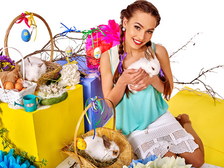 female animal: Woman with pigtails  keeps Easter eggs and group of rabbits in basket.