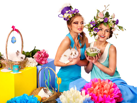 bunny girl: Two women friends in easter style keeps rabbits and flowers. Isolated. Stock Photo