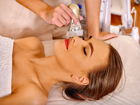 electrophoresis: Close up of lying young woman with closed eyes receiving electroporation  facial therapy at beauty salon. Stock Photo