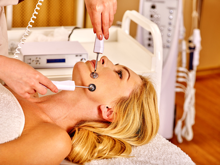 rf: Young woman receiving electric galvanic face spa massage at modern beauty salon. Stock Photo