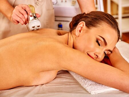 hight tech: Woman receiving electroporation back therapy at modern beauty salon.