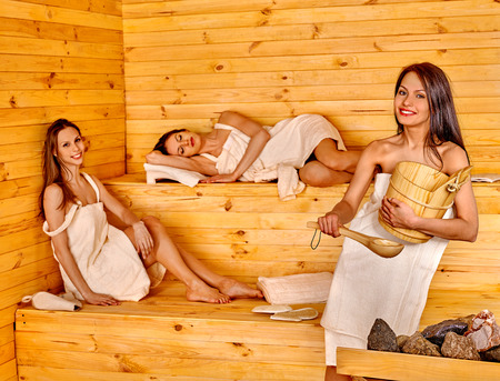 sauna: Happy girlfriends relaxing in sauna. Woman sitting and lying on bench. Stock Photo