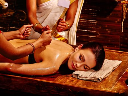 four hands: Two masseuses do massage in four hands into India spa salon.