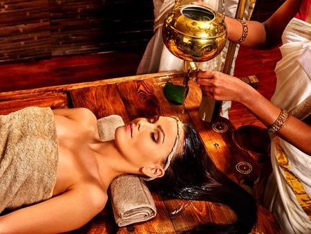 masaje: mujer joven que tiene la cabeza de aceite Ayurveda tratamiento de spa.
