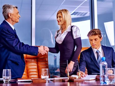 beguin: Happy business people in luxury office. Man handshake woman.