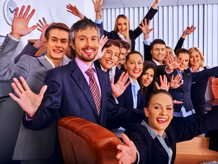 jalousie: Happy group business people with hand up together in office. Jalousie background. Stock Photo