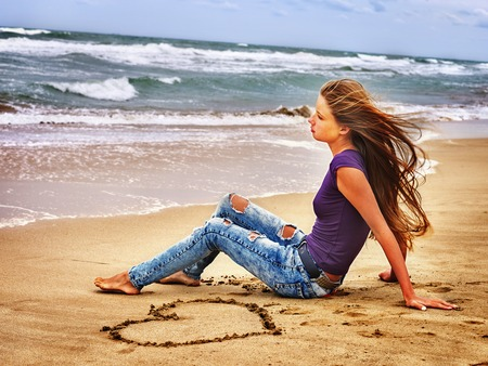beach blond hair: Summer girl sea.  Teenager draws heart on sand and  looks into the distance