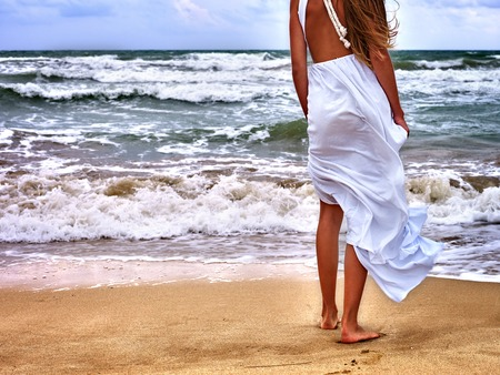 nude girl pretty young: Summer girl sea. Unrecognizable woman goes at water on coast. Back view. Stock Photo