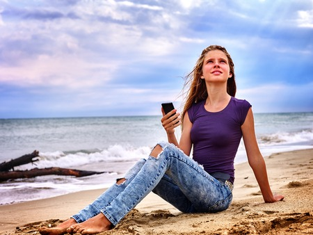 barefoot girls: Teenager on sand near sea call help by phone. Summer girl sea back on water. Sos. Stock Photo