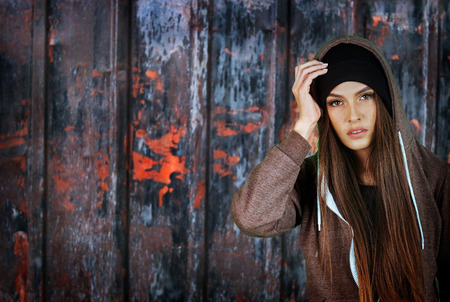 brunette girl: Teenager girl hipster on rusty fence background. Wearing hood. Stock Photo