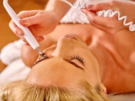 rf: Close up of  woman head receiving electric facial eyes massage on microdermabrasion equipment at beauty salon.