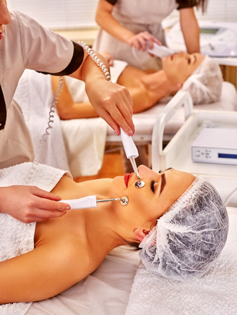 electrical equipment: Group of friend women receiving electric galvanic face spa massage procedure by two beauticians at beauty salon.