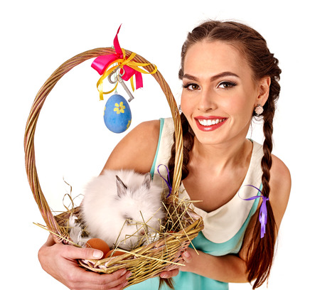 Concept of woman keeps easter eggs and rabbit in basket. Isolated.