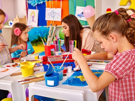 Les enfants avec une belle jeune peinture femme professeur sur papier à grande table ensemble à la maternelle.