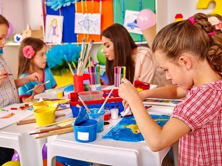 niños en la escuela: Los niños con pintura joven bella mujer del profesor en el papel en la tabla grande juntos en el jardín de infantes.